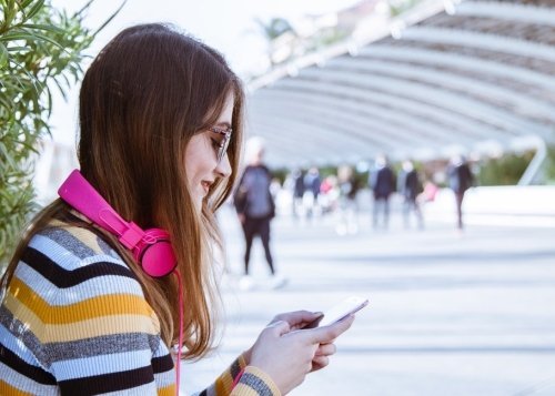 chica-mano-movil-auriculares-1300x650